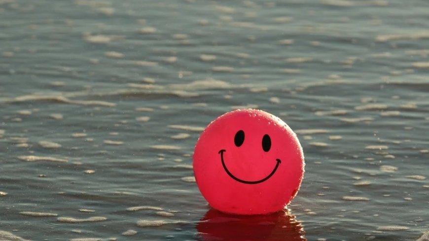 Czerwona piłka z uśmiechem unosząca się na wodzie.