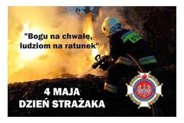 """Zdjęcie przedstawiające strażaka, gaszącego pożar opatrzone mottem"""" Bogu na chwałę, ludziom na ratunek"""", napisem 4 MAJA DZIEŃ STRAŻAKA i naniesionym znakiem Związku Ochotniczych Straży Pożarnych RP."""