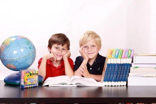 Dwóch chłopców siedzi w ławce, na ławce widoczny globus, zeszyty.