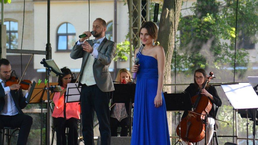 Zdjęcie ze sceny - w oddali orkiestra, na pierwszym planie wokaliści - mężczyzna i kobieta w eleganckich strojach.