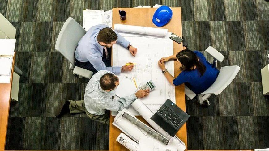 Zdjęcie z lotu ptaka - widok na rozłożone na biurku dokumenty. Przy biurku siedzi dwóch mężczyzn oraz kobieta.