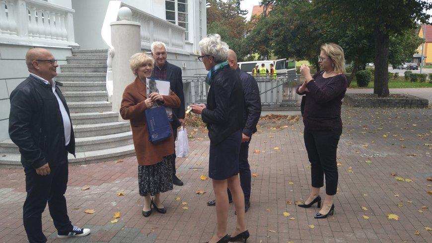 Otoczona przez ludzi Marion Mittenzwey stoi z upominkami przed Willą Wagenera