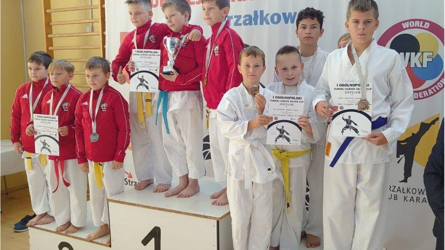 Zawodnicy w strojach karate stojący na podium